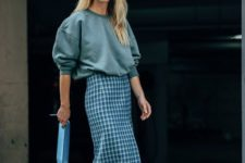 an oversized grey sweatshirt, a blue checked midi skirt, blue strappy heels and a blue clutch