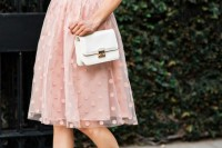 a white oversized tee, a pink polka dot knee skirt, nude shoes and a white crossbody bag