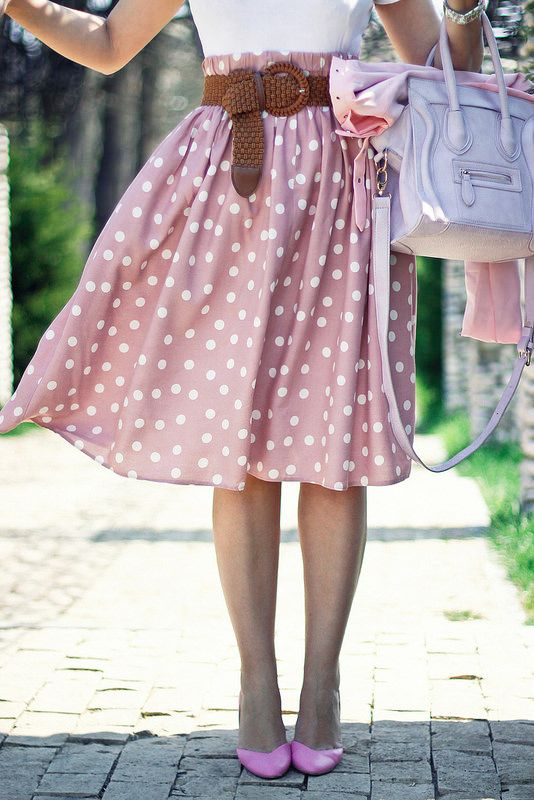 a white top, a pink polka dot midi skirt, a brown belt, pink shoes and a grey bag