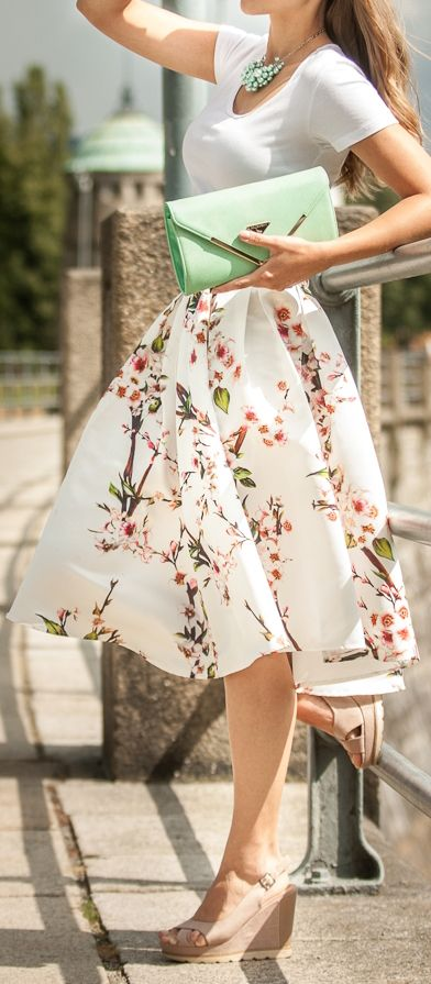 a spring to summer outfit with a white tee, a floral A-line midi skirt, nude wedges, a green cluth and a statement necklace