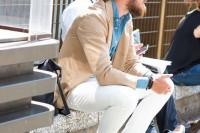 a chambray shirt, a tan blazer, white pants and brown moccasins for a stylish and fashionable look