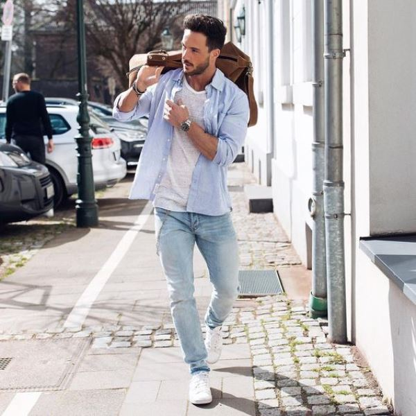 a white top, a blue shirt, blue jeans and white sneakers plsu a brown bag for a comfy outfit