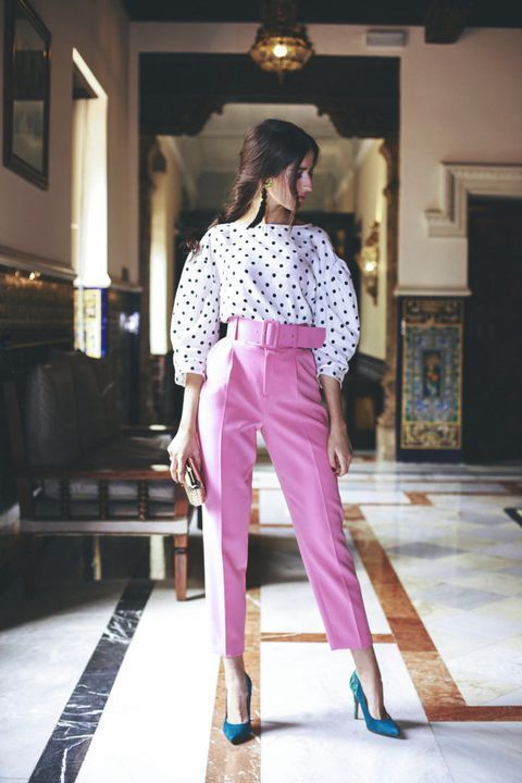 a bold outfit with pink high waisted pants, teal shoes, a polka dot blouse and a clutch