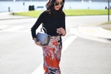 a bright spring work look with a black turtleneck, an abstract print midi, white shoes and a silver bag
