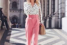 a bright spring work outfit with a white polka dot shirt, pink pants, white shoes and a tan bag to rock