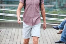 a mauve printed short sleeve shirt, off-white shorts, gren suede shoes and a backpack