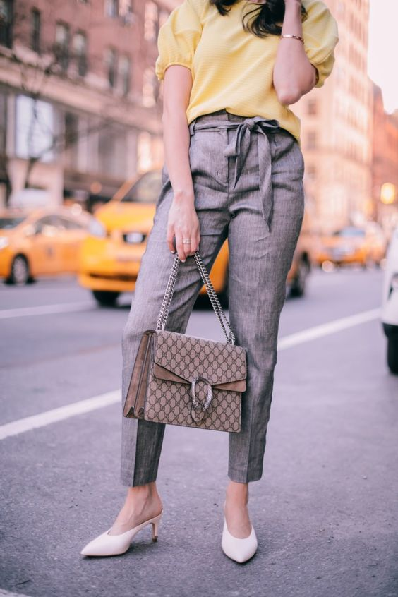 a spring work outfit with a yellow top with puffy sleeves, grey pants, white mules and a printed bag