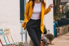 a summer work outfit with a white top, polka dot pants, a marigold blazer, black shoes and a black bag