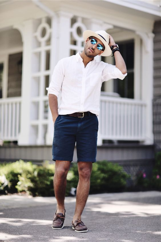 a white long sleeve cuffed shirt, navy shorts, brown shoes and a hat for vacation