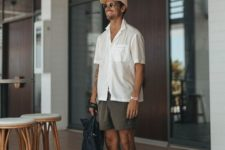 a white oversized short sleeve shirt, grey shorts, slippets and a cap for a hot summer day