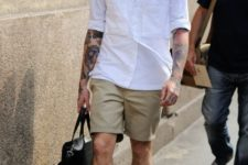 a white shirt with pockets, a white top under it, tan shorts, printed shoes and a black bag