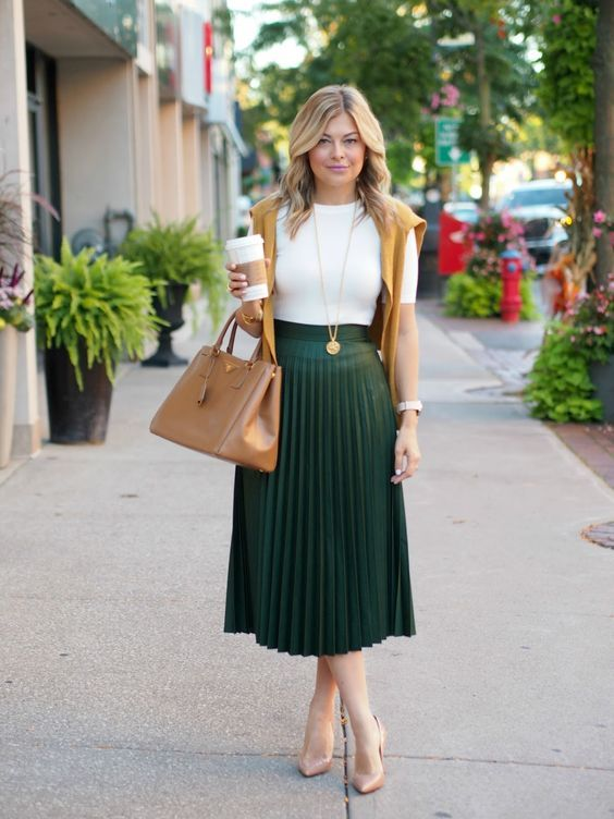 a white tee, a dark green pleated midi, tan shoes, a tan bag and a mustard sweater
