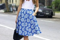 a bold outfit with a white tee, a blue printed A-line skirt, blue shoes and statement necklaces for summer