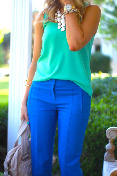 a colorful look with a green top, bright blue pants, statement necklaces and a neutral bag that matches