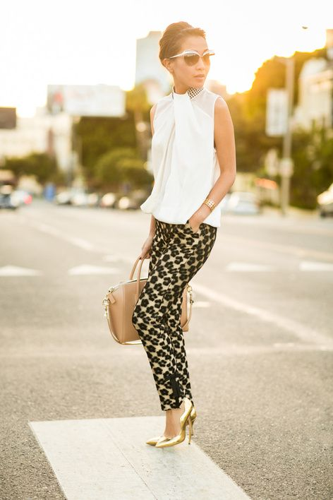 a white sleeveless tee with a printed collar, printed pants, gold shoes and a tan bag plus retro glasses