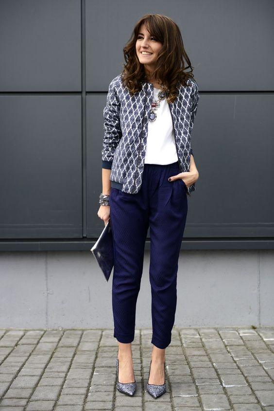 a white tee, navy pants, a printed blazer, statement necklaces and blue printed heels and a clutch