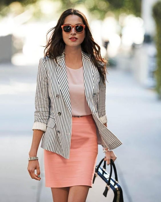 a blush top, a peachy skirt, a striped blazer, a two tone bag and cool retro sunglasses
