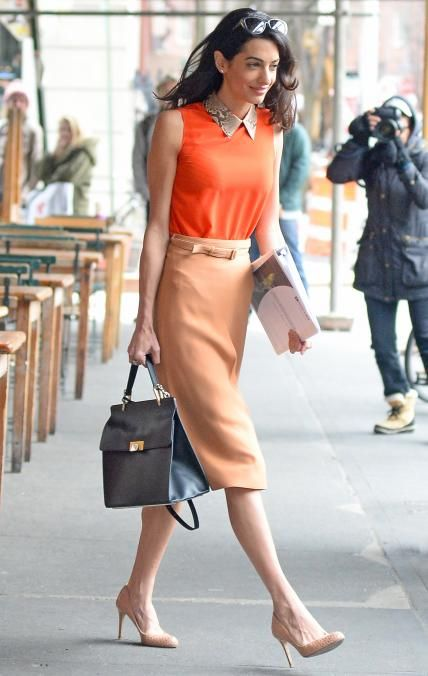 Amal Clooney wearing a tan pencil midi, an orange sleeveless short, nude shoes and carrying a black bag