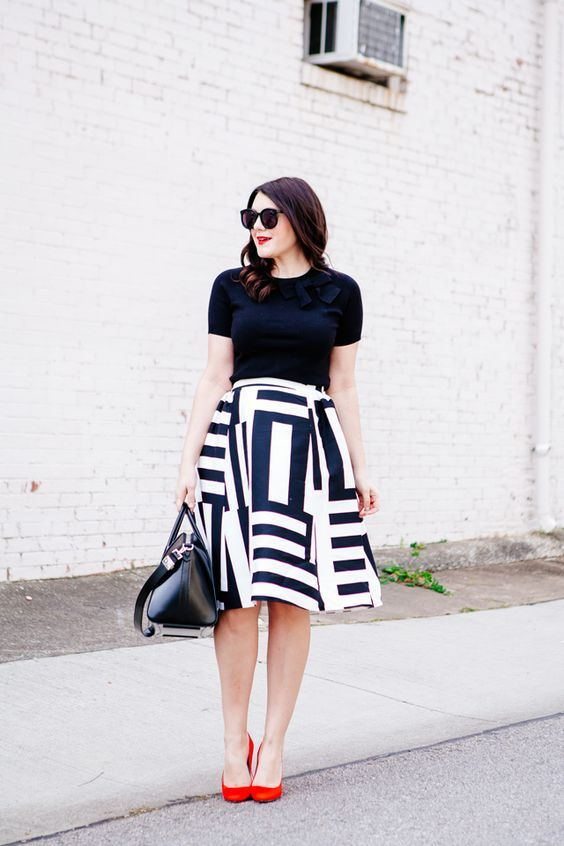 a monochromatic look with a black tee, a printed A-line skirt, red shoes and a black bag for work