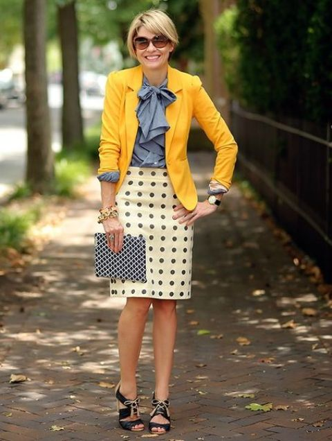 a grey bow shirt, a printed knee skirt, a sunyn yellow blazer, black lace up shoes and a printed clutch