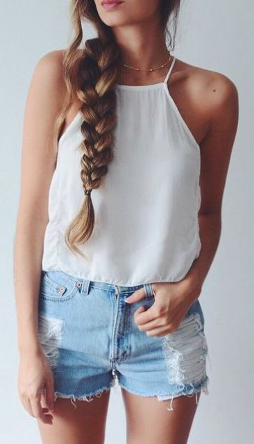 a white top and distressed denim shorts