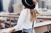 Raw Hem Jean Shorts With A White Blouse And Fedora Hat