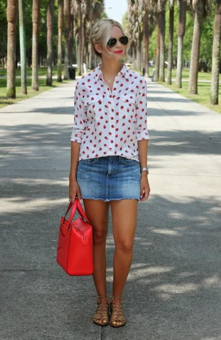 strawberry print blouse with a denim skirt and a red bag