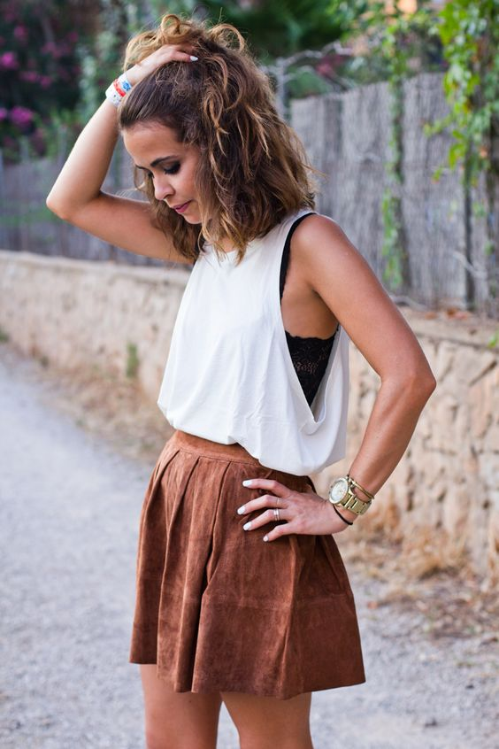 black lace top, a white top on it and a brown faux leather skirt