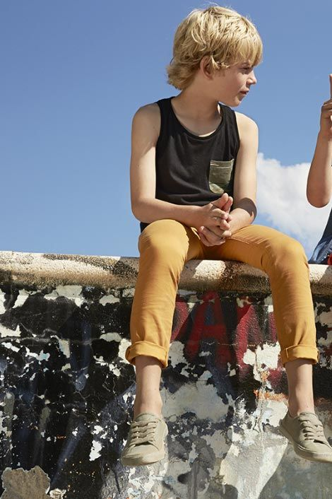 yellow pants and a sleeveless tee with sneakers