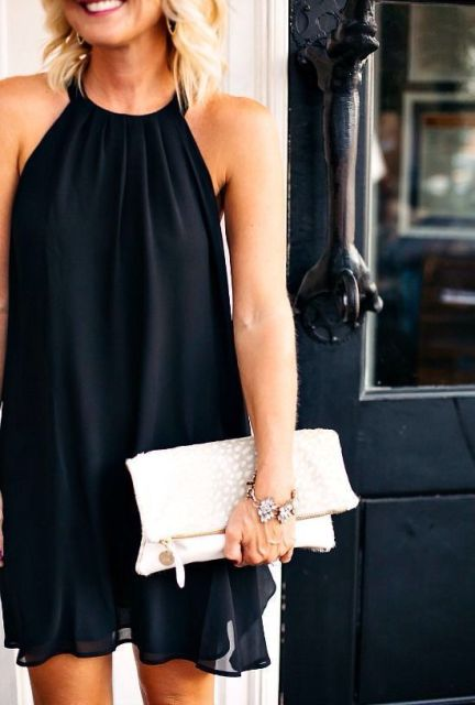 Simple black halter dress with white clutch
