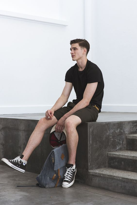 brown shorts, a black tee and black sneakers