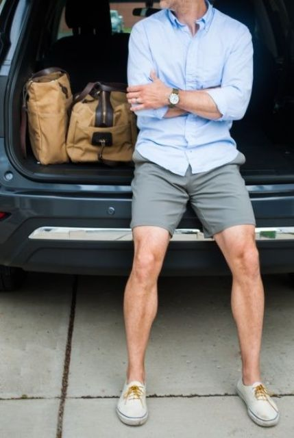 grey shorts, a blue shirt and beige vans