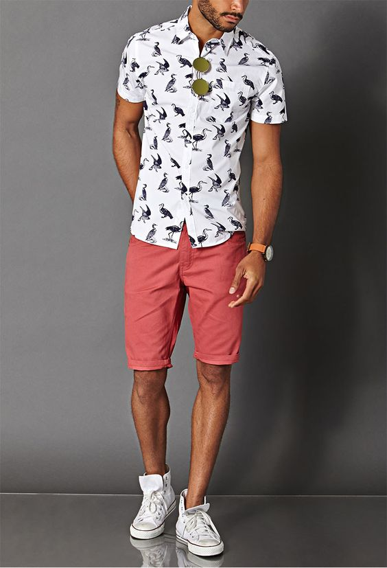 coral shorts, a printed shirt and white sneakers