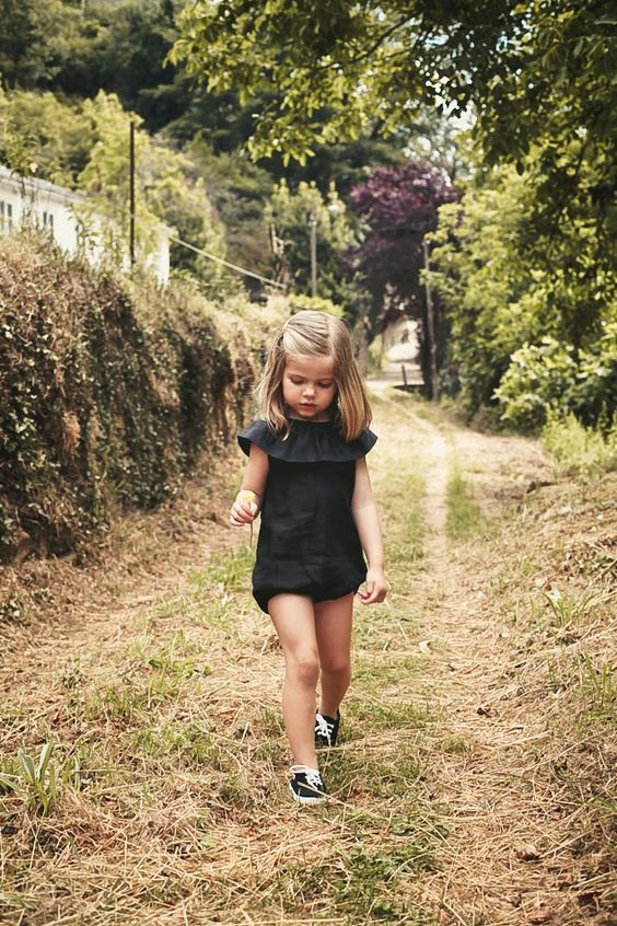 black ruffled sunsuit and black sneakers