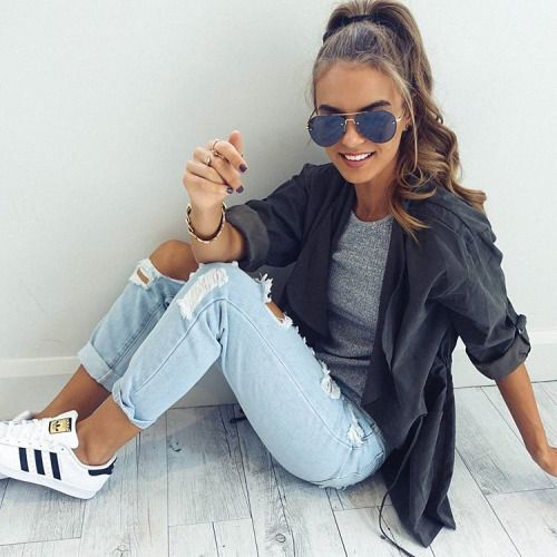 distressed jeans, a grey top and a black shirt with white sneakers