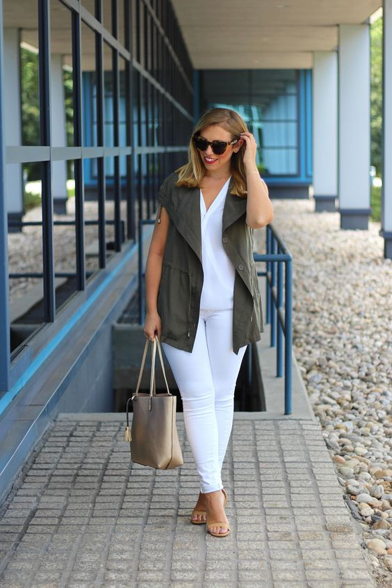 white jeans, a white top, an olive green vest and nude flats