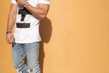 16 distressed blue jeans, a printed white tee and black vans