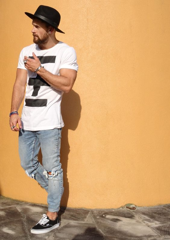 distressed blue jeans, a printed white tee and black vans