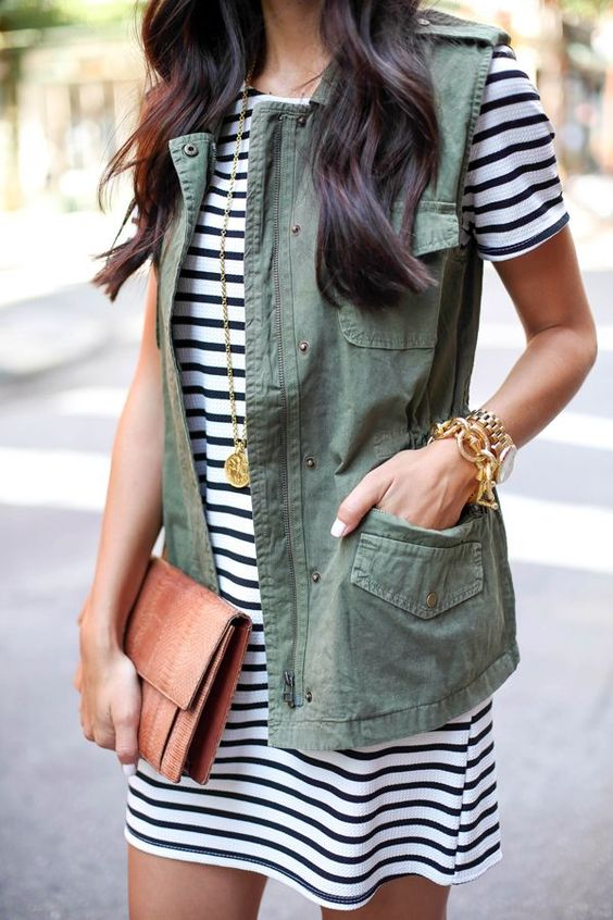 a striped dress, a military vest and a tan leather clutch