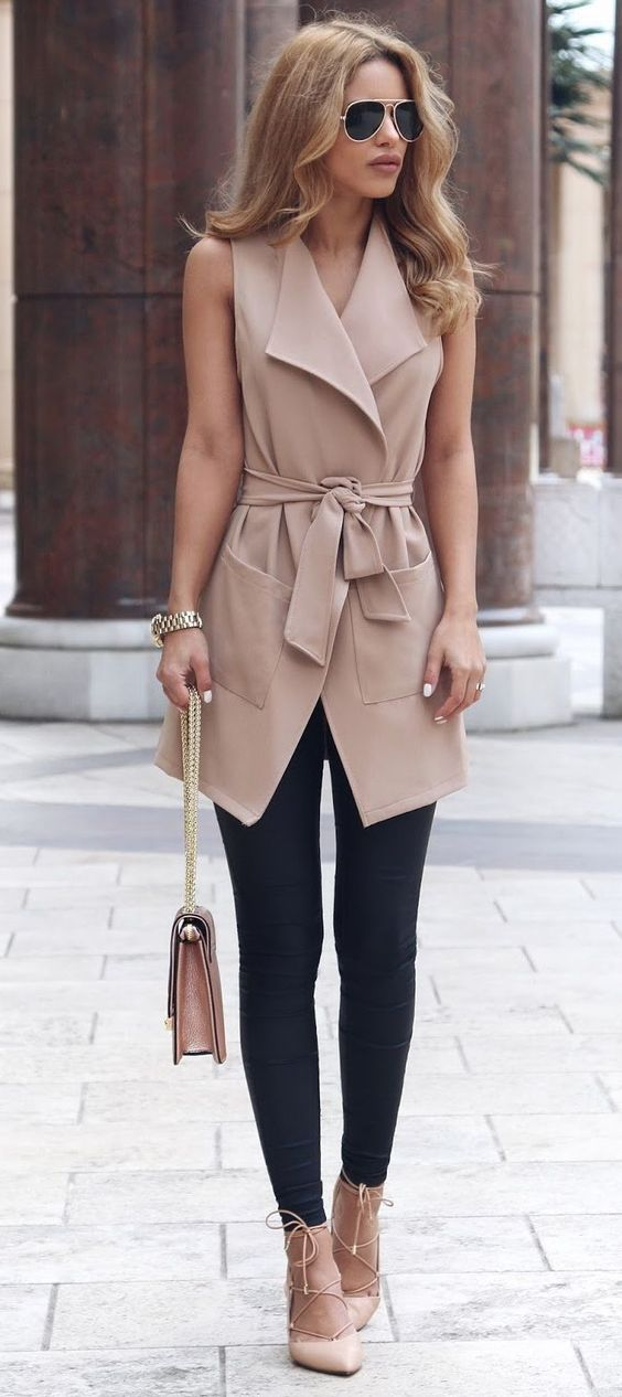 black leggings, a long tan vest, tan lace up heels