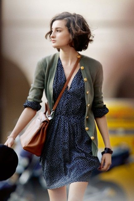 navy polka dot dress, a green cardigan and a tan corssbody