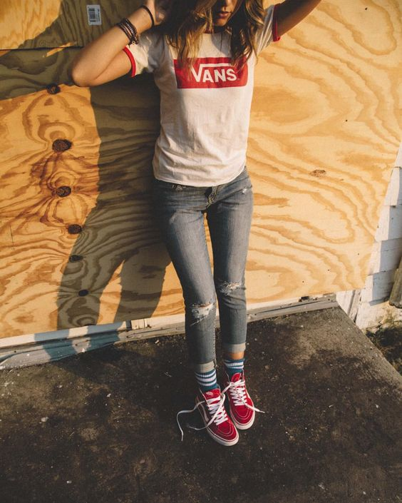 distressed jeans, a Vans tee and red sneakers