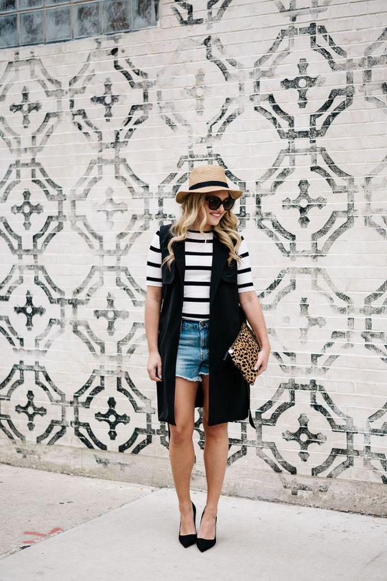 a striped tee, denim cutoff shorts, a long black vest, black Pumps, a leopard clutch