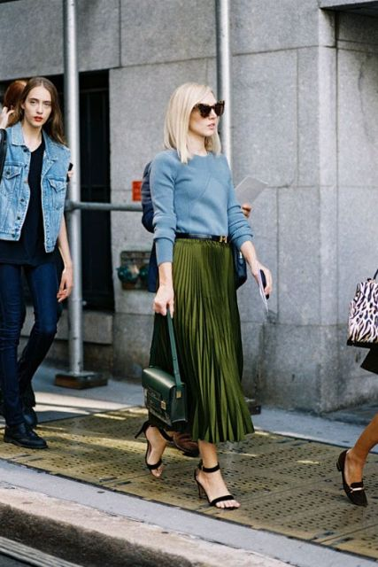 Fashionable look with light blue sweatshirt and pleated olive green midi skirt