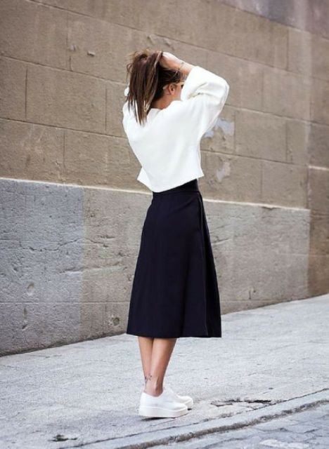 Look with white loose shirt, black midi skirt and slip on shoes