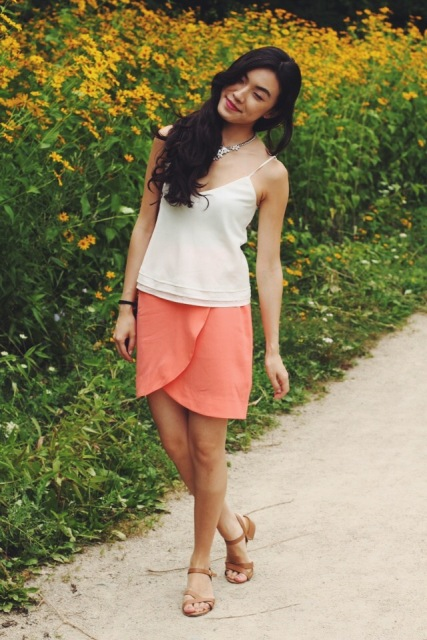 With airy white top and flat sandals
