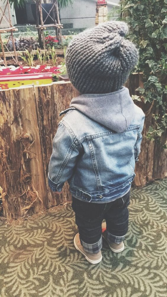 a dehim jacket, jeans, a hoodie, a knit hat and brown sneakers
