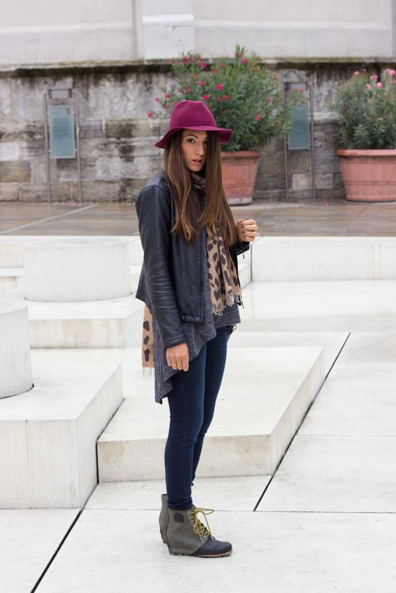 a leather jacket, navy jeans, boots and a purple hat
