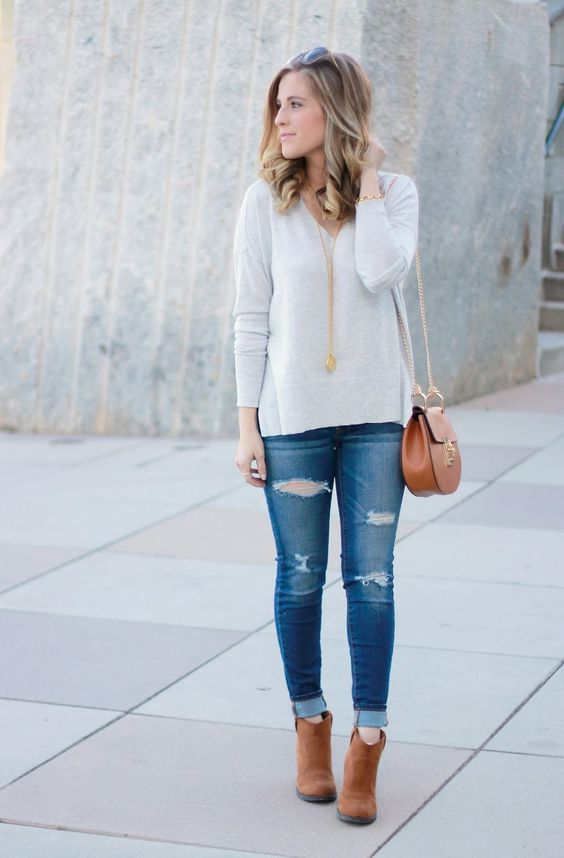 a grey sweater, jeans, cognac booties and a bag, gold accessories