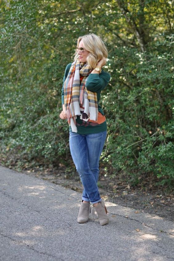 a plaid blanket scarf, a green sweater, skinny jeans and booties
